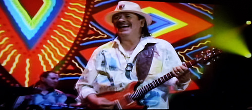 Carlos Santana playing guitar on stage in front of a bright set, Jazz - an example of vibrant culture, hand painted shirt - photo shot from TV, Guadalajara, Jalisco, Mexico